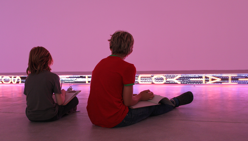 Two people seating on the floor enjoying exhibition