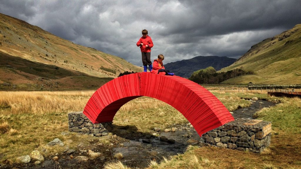 Two children perched on Paper Bridge by Steve Messam in Cumbria