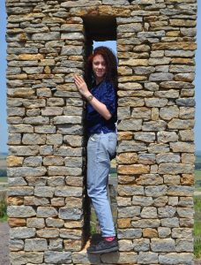 Teenage girl smiling at camera and standing in a tight gap in one of the rectangular stone structures that make up the stone circle. It's made of sand coloured bricks.