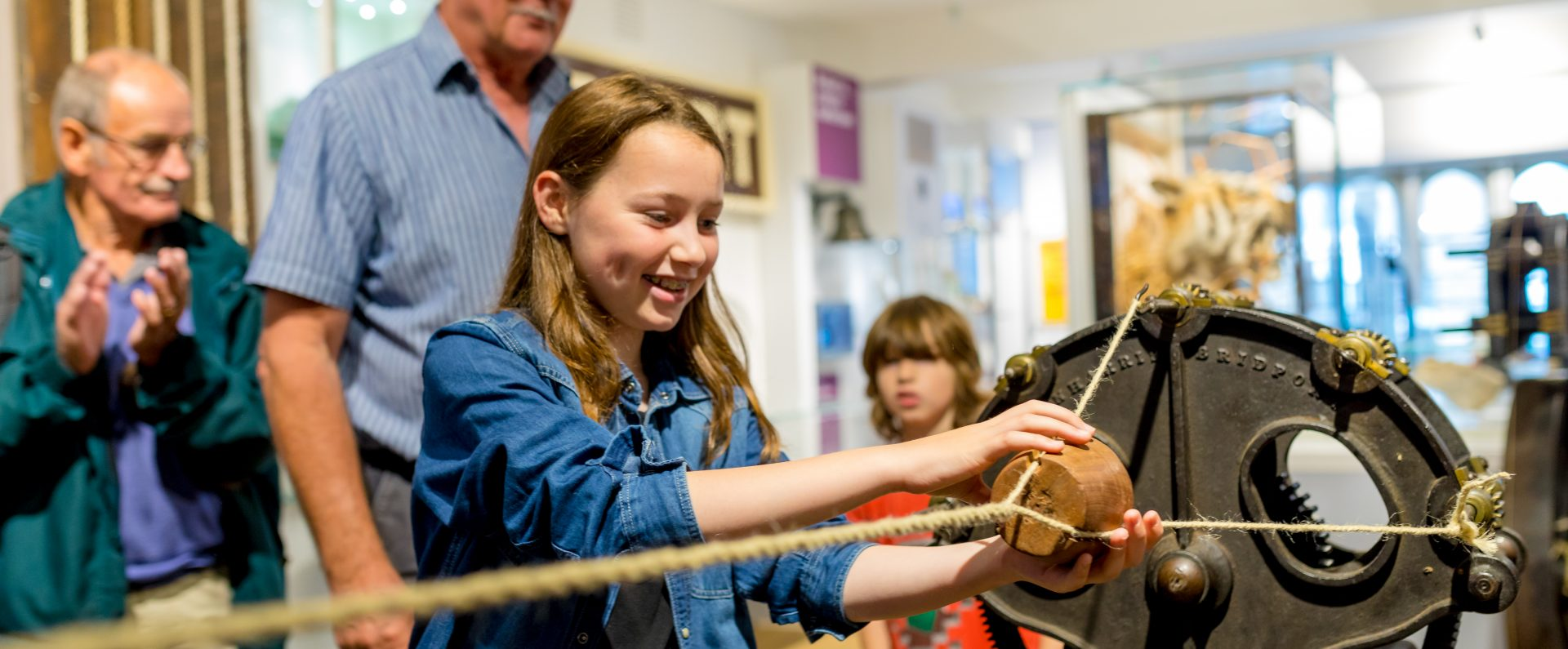 Visitors young and old enjoying learning about the history of rope making at Bridport Museum