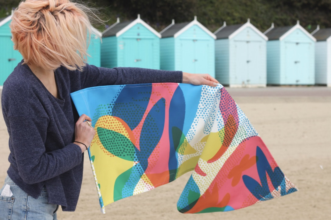 Illustrator Bel Burkill holding up her deck chair print design on Bournemouth Beach