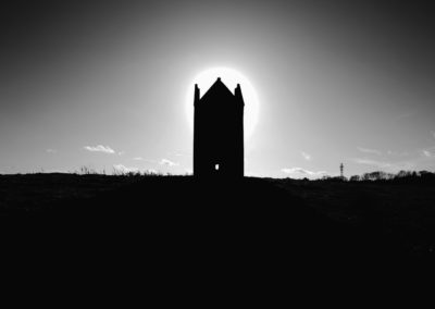 A black and white photograph of a silhouette of a tower against the bright sun.