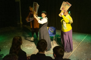 Two women are on a dark stage lit by dim green lights. They are dressed as suffragettes and hold placards and are shouting at the audience.