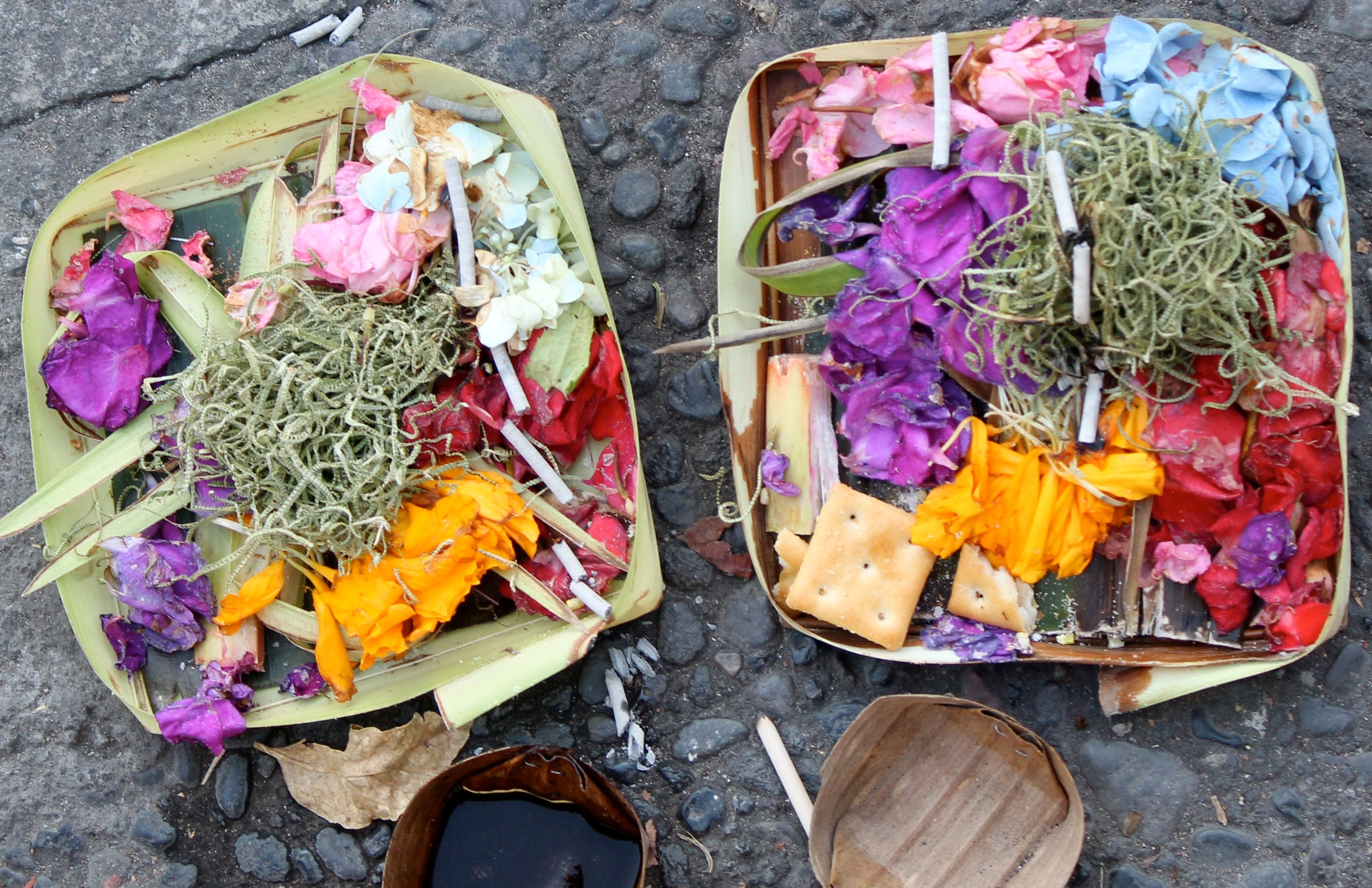 Small baskets full of different colours, pink, red, blue full of Balinese Offering