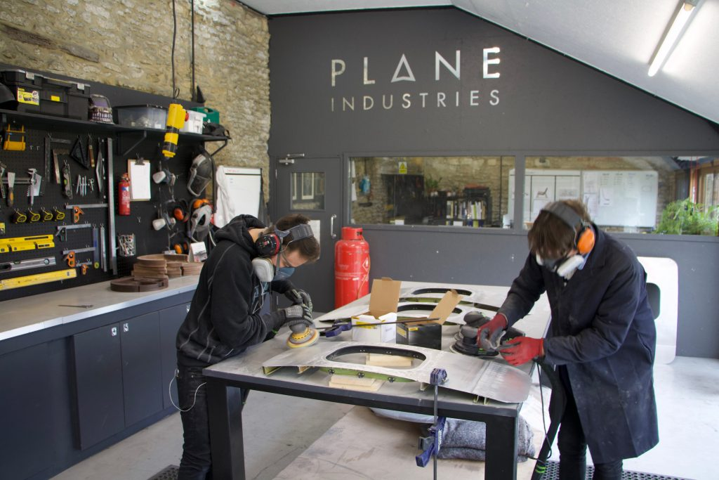 two people sanding a piece of metal in the plane industries workshop