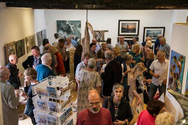 A room full of people with artworks on the wall