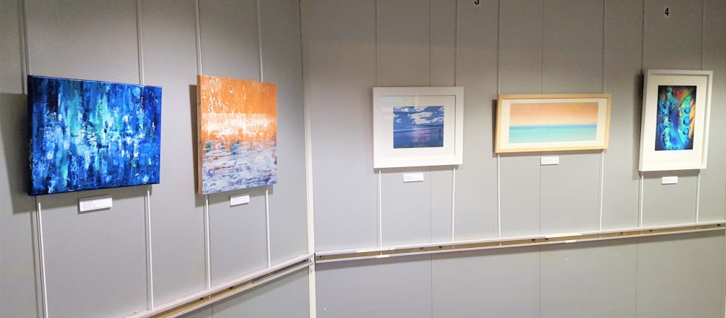a picture of five paintings on a grey wall on the Barfleur Ferry