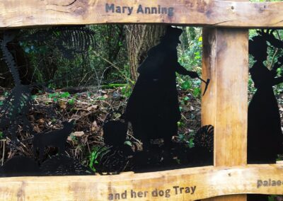 A wooden fence with rough, natural edges with text burnt into it that reads 'Mary Anning and her dog Troy'