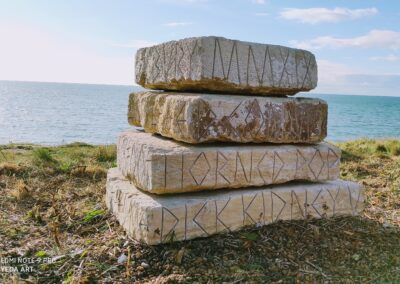 Four grey/white rectangular stones stacked on top of one another. The edge facing us has thin characters