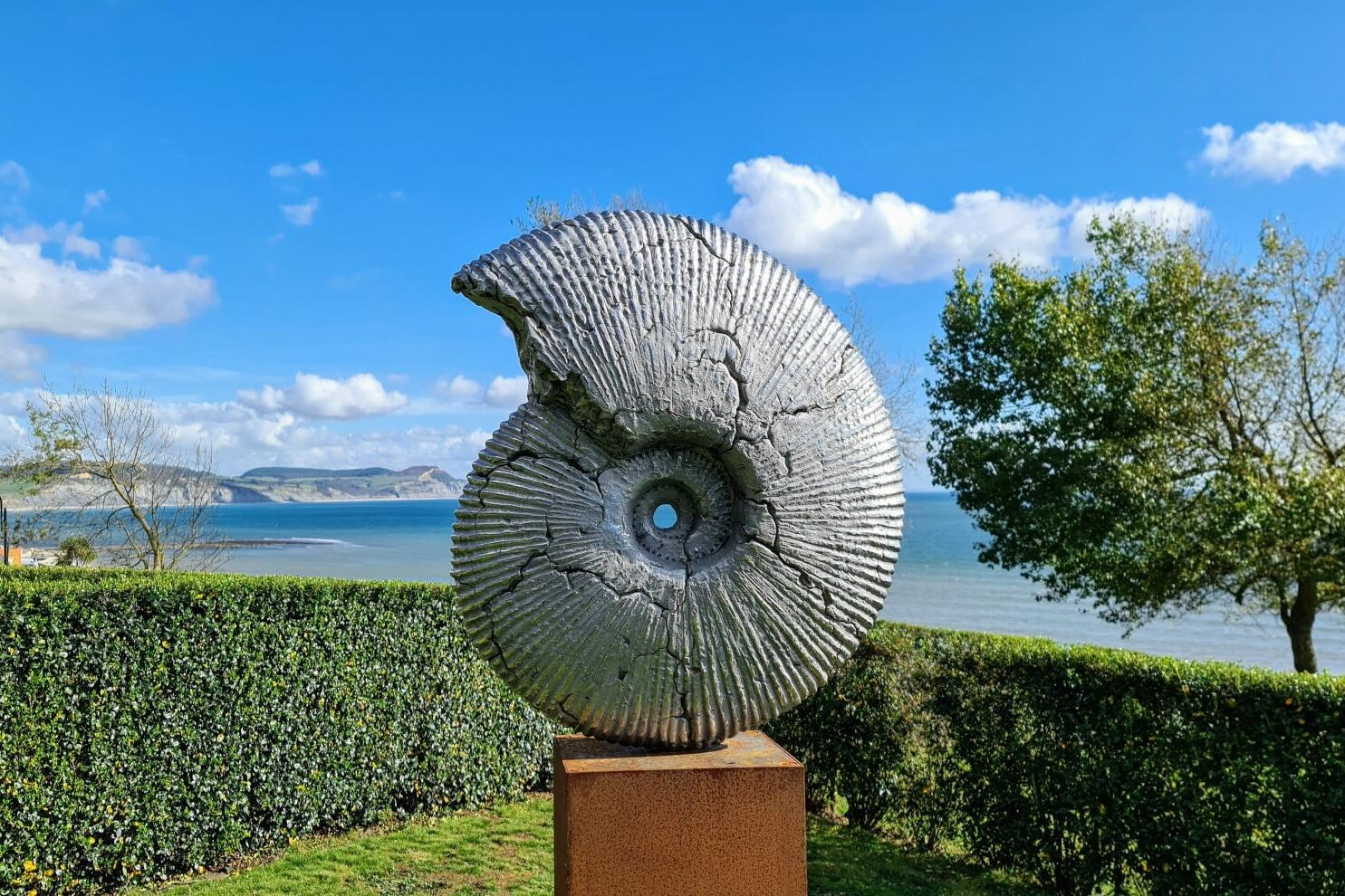 A sculpture of an annomite, a fossilised spiral shell of an ancient squid-like creature. It's cracked and sits on a wooden plinth against a sunny backdrop of the gardens, sea and blue skies