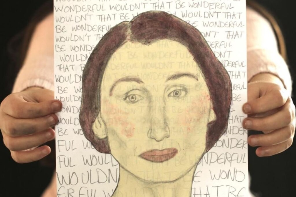 two hands holding a painted portrait of a woman with brown hair. there is text in the background written with pencil
